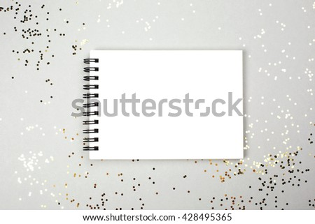 Paper note book with white pages lying on festive background with little golden sparkles. Place for text. - stock photo