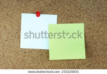 Paper note pads on cork board. - stock photo