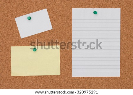 Paper note with pushpin on cork board background.