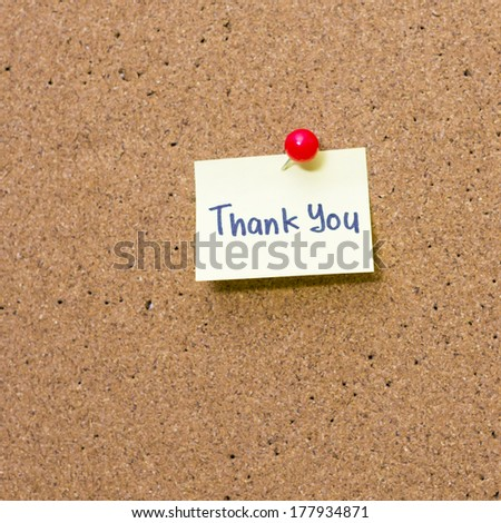 Paper note with word Thank You pinned on cork board - stock photo