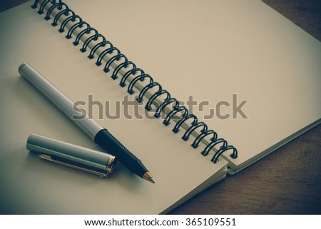 paper notebook and pen on a table with filter effect retro vintage style