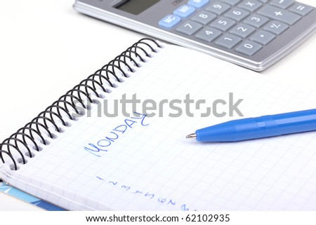 Paper notebook with calendar and calculator in distance, closed-up