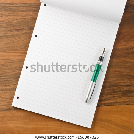 Paper notebook with pen on wooden background   - stock photo