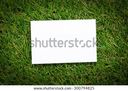 paper on green grass background - stock photo