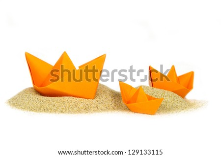 paper origami boats run aground (sand island) isolated - stock photo