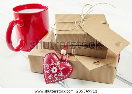 Paper parcels wrapped tied with tags. A milk mug for Santa, a red heart and some  christmas gift boxes with paper kraft and tied with red & white baker's twine on a white wooden table. Vintage Style. - stock photo