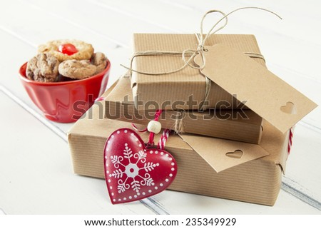 Paper parcels wrapped tied with tags. Cookies, a red heart and some christmas gift boxes wrapped with paper kraft and tied with red & white baker's twine on a white wooden table. Vintage Style. - stock photo