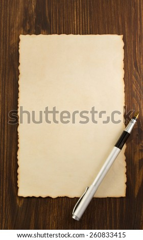 paper parchment and ink pen on wooden background - stock photo