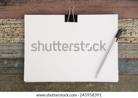 Paper pen and clip on vintage wood for background and text - stock photo