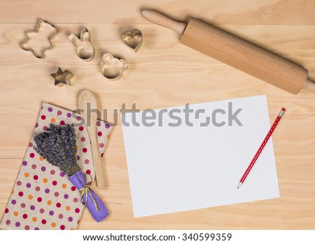 paper, pencil and some kitchen utensils on wooden background - stock photo
