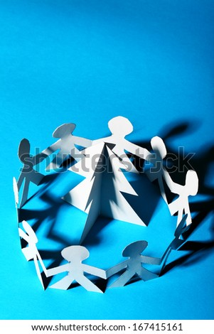 Paper people dancing around Christmas tree and space fot text at the top - stock photo
