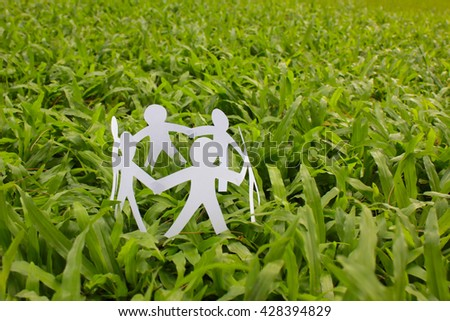 Paper people in a circle with green grass background. world peace concept. - stock photo