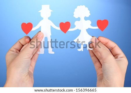 Paper people in hands on blue background - stock photo
