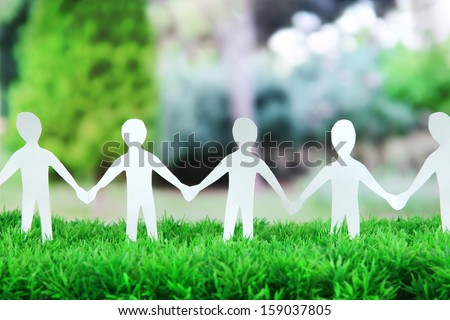 Paper people in social network concept on green grass outdoors - stock photo