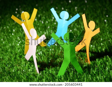 Paper people on green grass, close up - stock photo