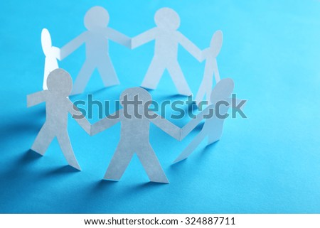 Paper people on the blue paper background - stock photo