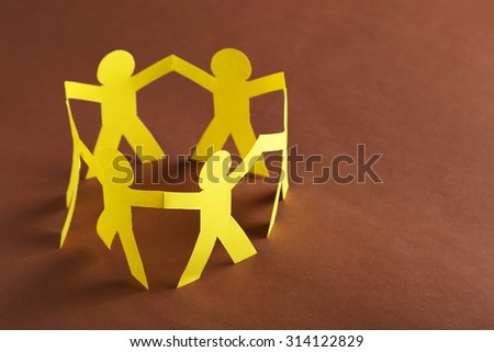 Paper people on the brown paper background - stock photo
