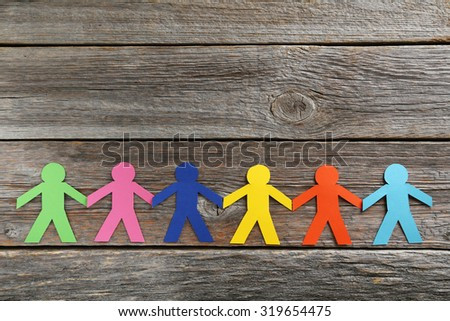 Paper people on the grey wooden background - stock photo