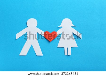 Paper people together in love on the blue background - stock photo