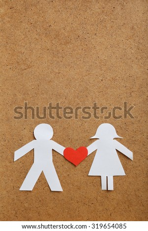 Paper people together in love on the brown background - stock photo