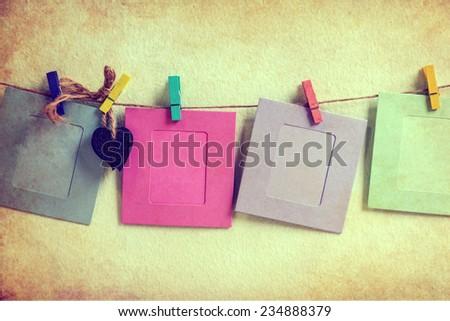 paper photo frame on clothesline over grunge background, Valentine concept - stock photo
