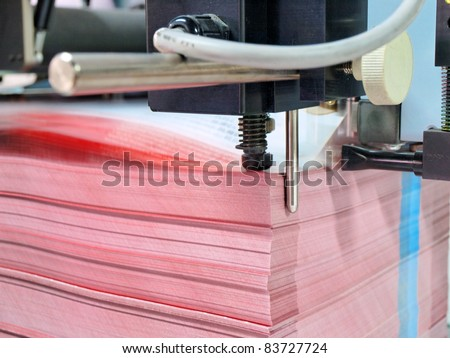 paper pile in a finishing, folder station in an offset printer - stock photo