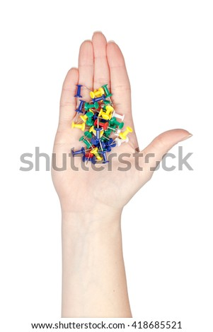 paper pins in a hand isolated on white background. school and office tools. stationery - stock photo