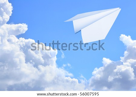 Paper plane flying against sky and clouds in the background