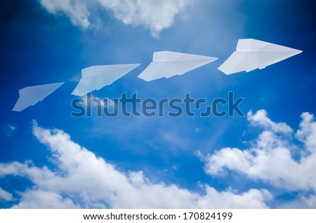 paper plane flying in blue sky - stock photo