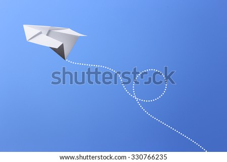 Paper plane flying in the blue sky. - stock photo