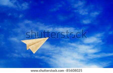 paper plane flying on blue sky - stock photo