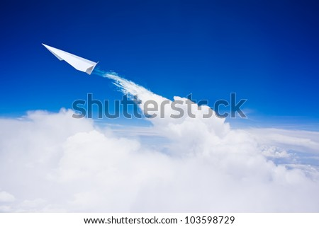 Paper plane flying over clouds against blue sky - stock photo