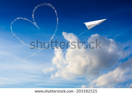 Paper plane flying with the heart shape in the sky  - stock photo