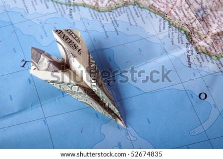 Paper plane on travel map symbolizing and expensive journey - stock photo