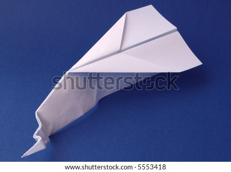 Paper plane with damaged nose on blue background; concepts: crash, failure, business failure - stock photo