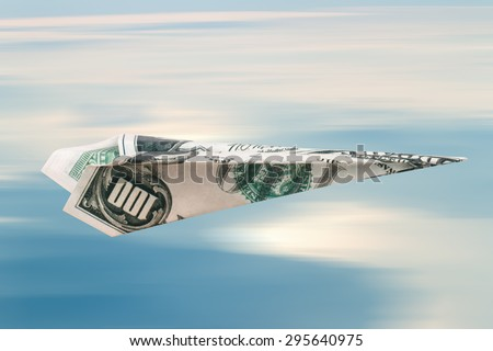 Paper plane with dollar banknote, on blue cloudy sky background. - stock photo