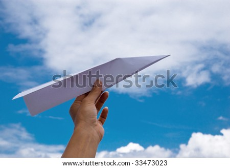 Paper plane - woman can't await holidays and launches a paperplane into the sky