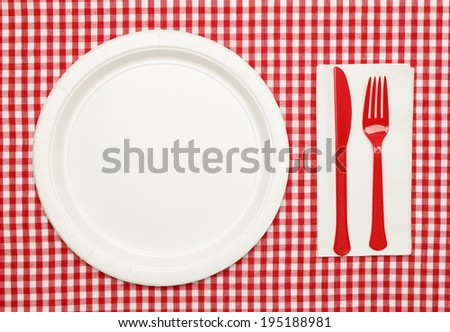 Paper Plate on Red Checkered Table Cloth with Plastic Utensils and Napkin. - stock photo
