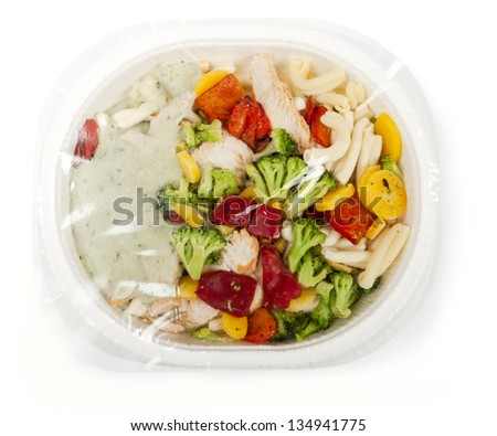 paper plate with prepackaged fast food with plastic foil on top. - stock photo