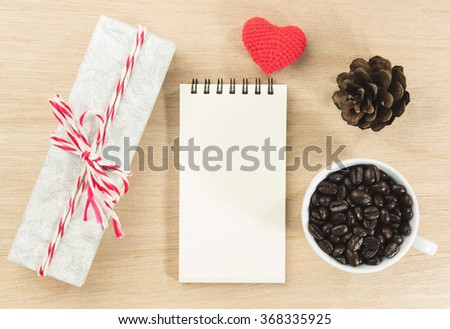 paper, red heart, gift box and coffee bean in white cup on wooden table. - stock photo