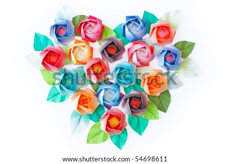 Paper roses arranged in a heart shaped on a white background - stock photo