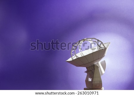 Paper scale model of the radio telescope antenna on a blue background - stock photo