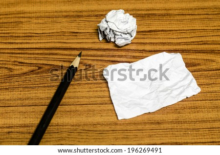 paper scrap and crumpled with pencil on wood background - stock photo