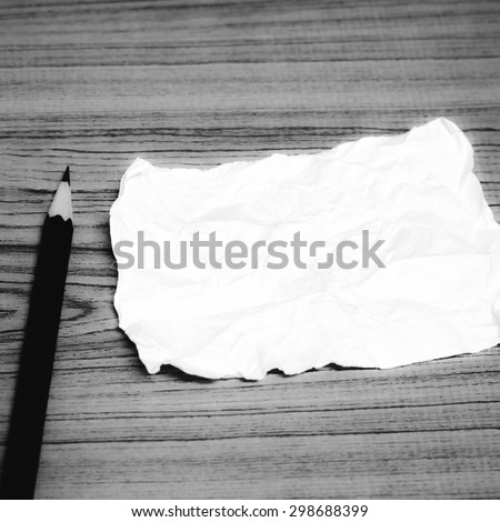 paper scrap with pencil on wood background black and white color tone style