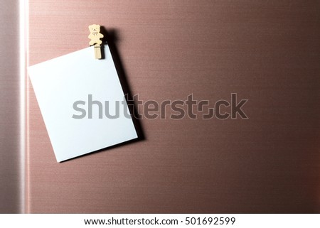 Paper sheet on refrigerator door with magnetic clip for add text