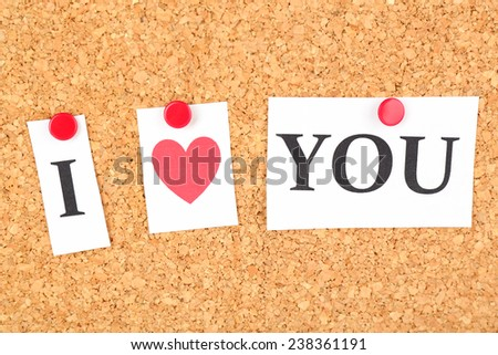 Paper sheets with declaration of love on wooden background - stock photo