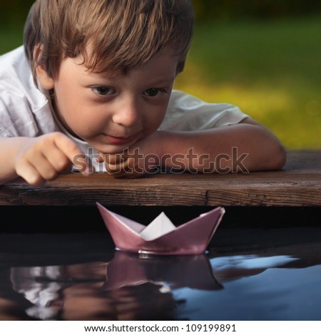 paper ship in children hand - stock photo