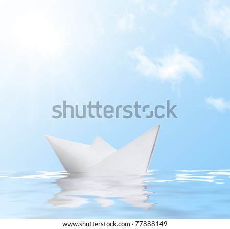 Paper ship in water with reflection against blue sunny sky - stock photo