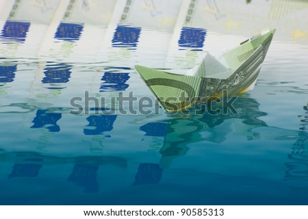 Paper ship made of euro banknote sailing on money - stock photo