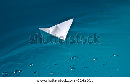 paper ship on blue waves - stock photo